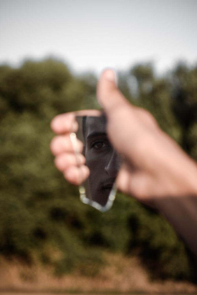 Man looking in broken mirror PTSD