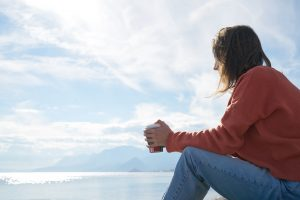 woman sitting by sea feeling depressed