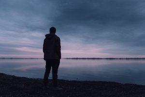 man standing by lake dusk