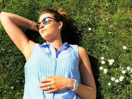 women in blue laying on grass in sun