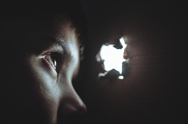 person looking through a hole in a dark wall