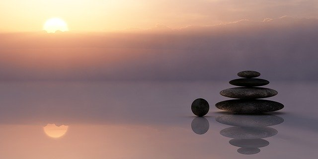 sunset on a lake with a stack of rocks