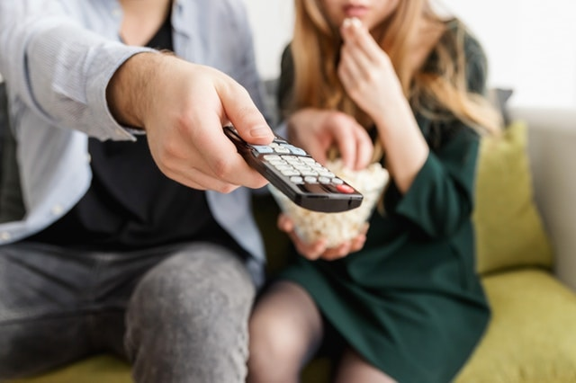couple watching home movie with remote
