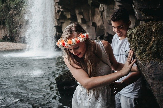 couple walking by a waterfall