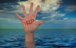 hand with help written on it reaching out of waterr