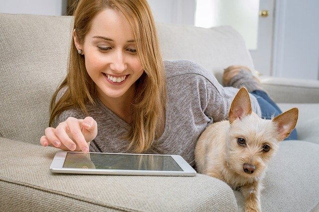 Woman at home on tablet with dog