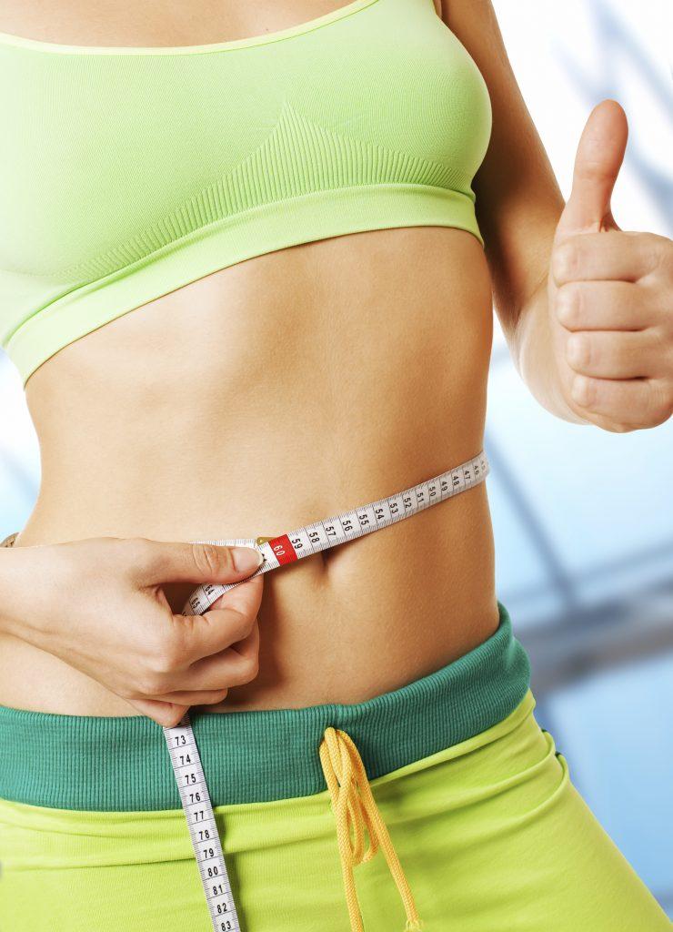 woman measuring waistline with tape measure