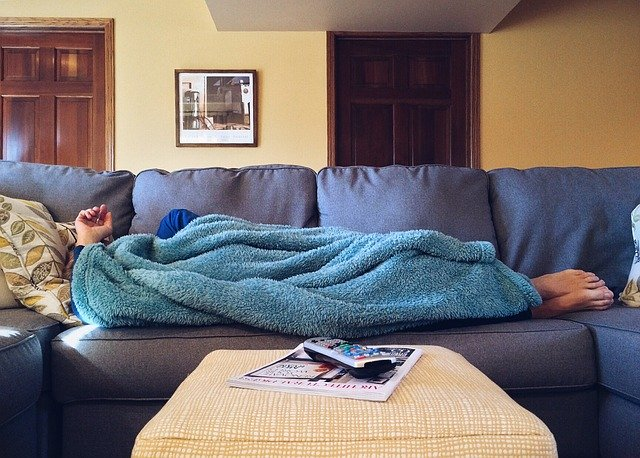 person lying on a couch wrapped in a blanket