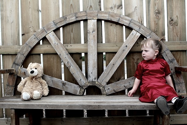 Bench with a child and a stuffed bear sitting