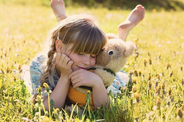 girl lying in field of yellow flowers hugging bear