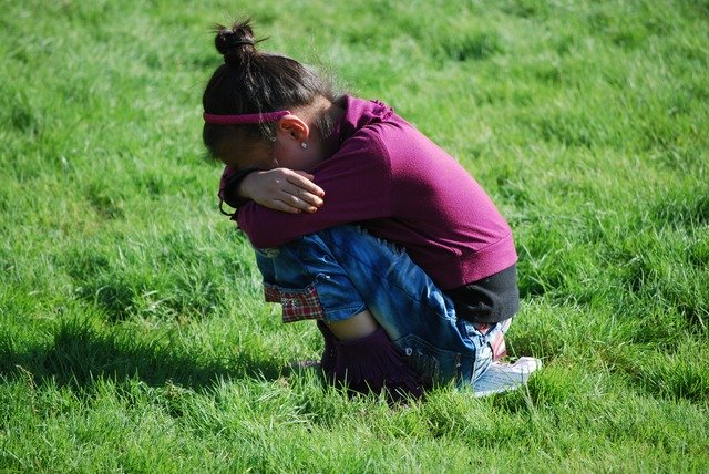 little girl crouched down in the grass