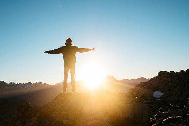person standing in suns rays with arms wide