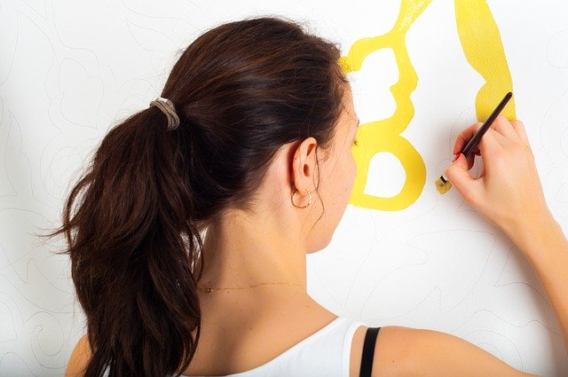 woman painting on the wall