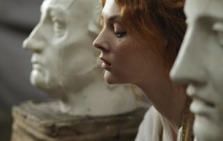 womans face between two face statues