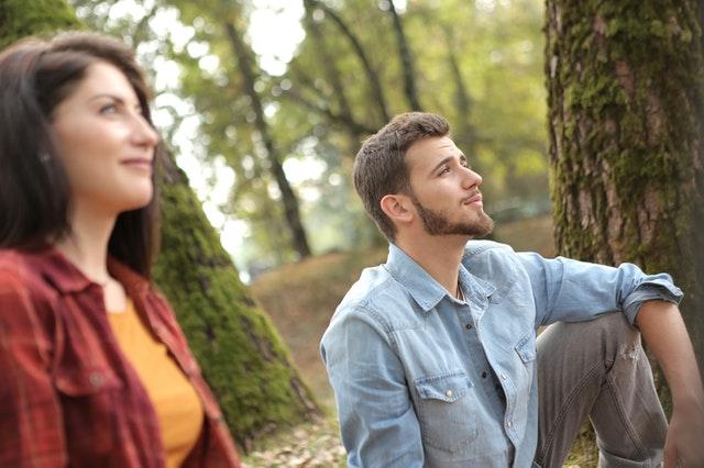 couple sitting under trees