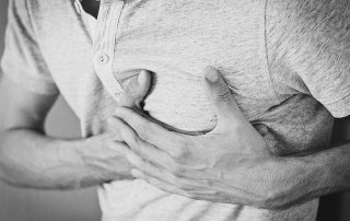 man grasping chest in pain