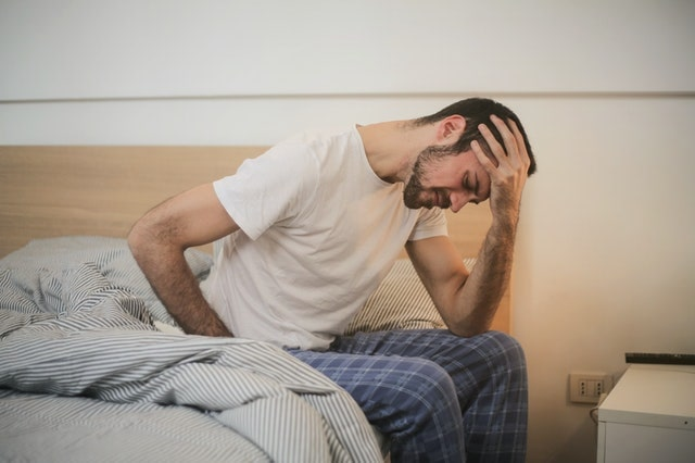 man sitting on bed with head in hands