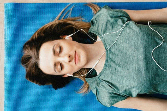 woman lying down with ear plugs